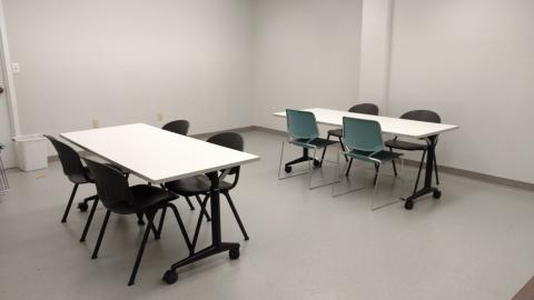 Small meeting room equipped with two rectangular tables with four chairs at each table