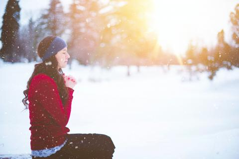 woman meditating in snow